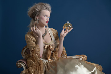 Retro baroque fashion woman wearing gold dress. Holding bottle o