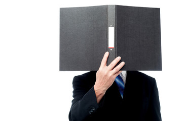 Businessman holding file pad and cover his face