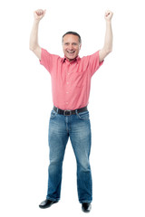 Happy man celebrating arms up success