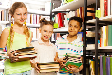 Three friends with books standing near bookshelf