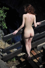 Naked girl standing on the bridge