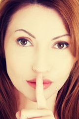 Woman with finger on her lips.