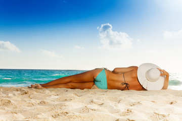 Tanned woman laying on white sand beach