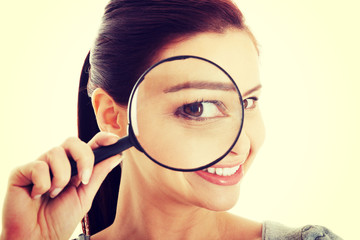 Young beautiful woman with magnifying glass.