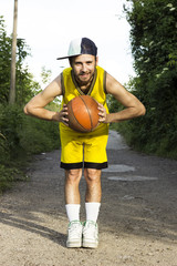 Young basketball player holding the ball in his hand outdoor