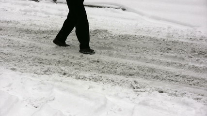 Person walking on the road covered with snow