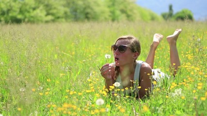 Young woman blowing dandelion seeds in field
