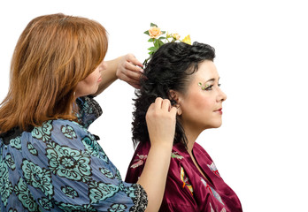 Red-haired hairdresser giving a new hairstyle to mature woman