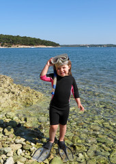 Portrait of happy girl with wetsuit and snorkels at the s