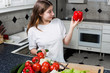 Young woman at kitchen looking at red pepper