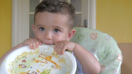 cute little child biting a plate