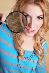 blondes Mädchen schaut durch eine Lupe