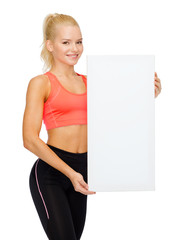 smiling sportswoman with white blank board