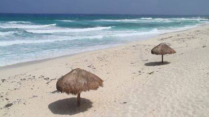 Sun umbrellas on a beach with waves (shot in Caribbean - Cozumel