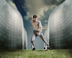 Man in casual suit playing in football near the modern building