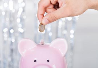 Man Inserting Coin In Piggybank