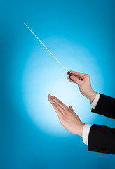 Musician Holding Baton Against Blue Background