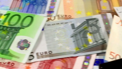 Euro money with a hand loupe in close dolly shot