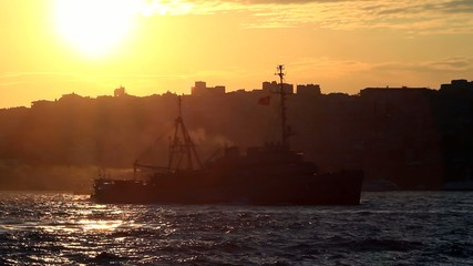 Sunset in the city. Ship passing in front of city silhouette