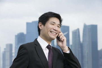 Happy Chinese business man talking on the phone in front of city