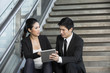 Asian Businessman and woman using tablet.