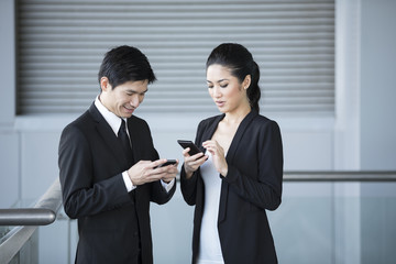Two Asian business colleagues using smartphone's.