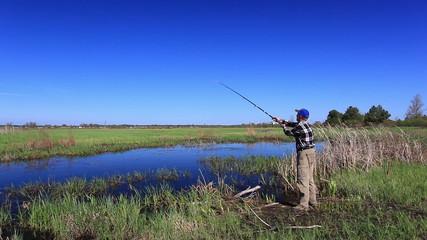 man  fisherman twists  fishing coil   near lake in  bright day