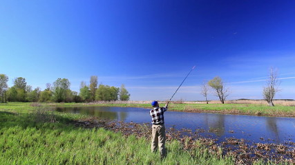 man  fisherman twists  fishing coil   near lake in  bright day