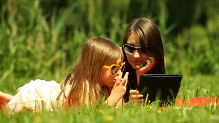 Picnic. Mother with daughter using tablet outdoor