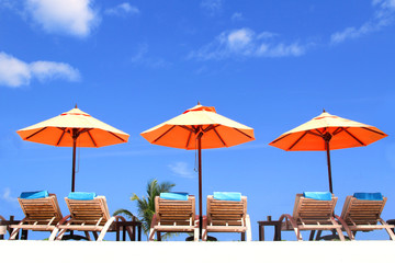 Beach chairs and umbellas with cloudy blue sky