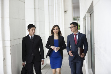 Asian Business colleagues walking outside.