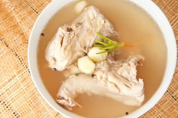 Chicken bone stock soup in bowl on mat