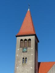 Kirchturm mit Turmuhr vor blauem Himmel in Helpup bei Detmold