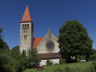 Wiese mit roter Parkbank vor der Kirche in Helpup bei Detmold
