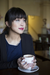 Portrait of a Asian woman in a cafe. Lifestyle image.