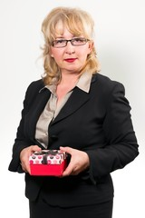 Portrait of a middle aged businesswoman, with present in hands.