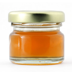 Glass jar of honey with lid isolated on white