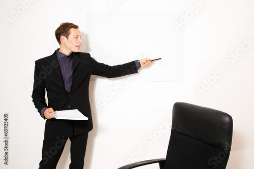 Young business dressed male holding presentation
