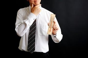 温度計を持っているスーツの男性