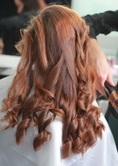 styling curls and weaving French braid on long hair in salon