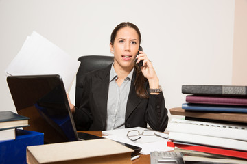 Young business dressed woman working at desk.