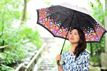 雨の日に傘を差している日本人の女性