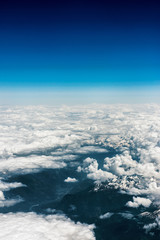 Above aerial plane view of Italian alps and cloudscape