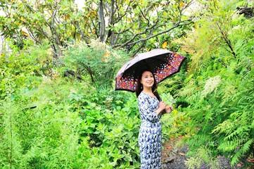 自然の緑の中で傘を差しているアジア人の女性