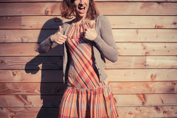 Young woman giving thumbs up outside wooden cabin