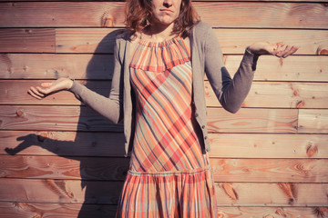 Confused young woman outside wooden cabin