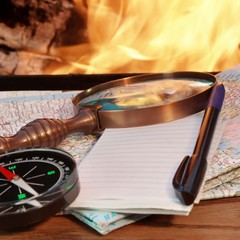 Road maps, Compass,  Notebook, pen and a magnifying glass