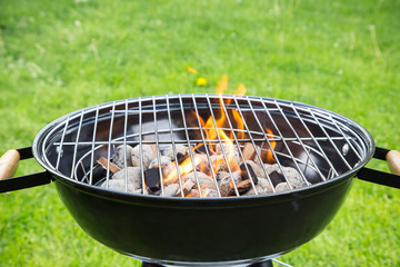 Empty burning grill on garden