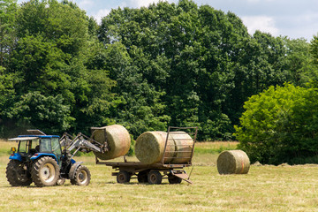 A tractor that charge a straw bale