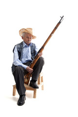Man in a hat sitting with a gun